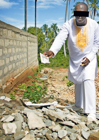 A pastor in Tanzania shows some of the rubble after his church was destroyed.