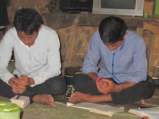 Two Christian men pray during a house church meeting in Laos.