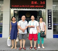 Pastor Li Wanhua (second from left) in front of a police station.