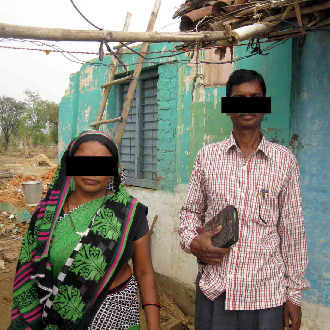 Anaram Bokar and his wife stand in front of their demolished living space.