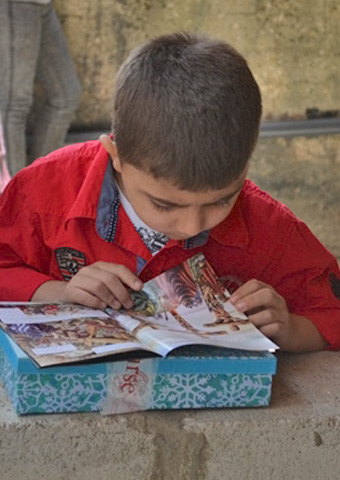 A Syrian child eagerly reads one of the children's Bible stories received during a distribution to refugees.