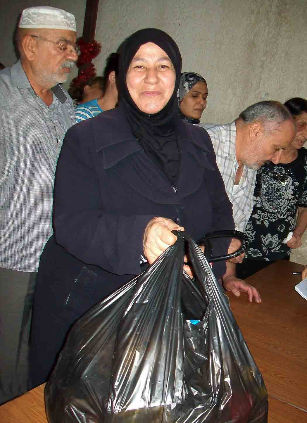 An aid recipient is overjoyed to receive a food package.