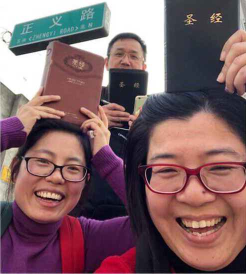 The spouses of arrested believers held Bibles over their heads while protesting outside the German embassy.