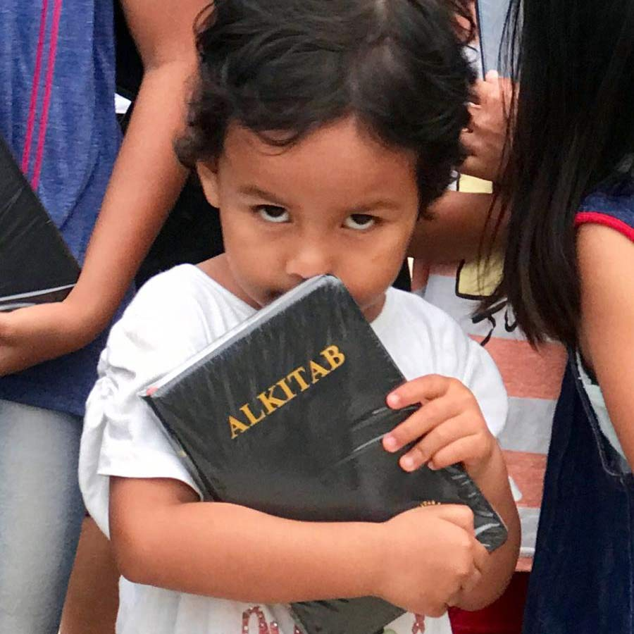A child is deeply grateful for one of the new Bibles.