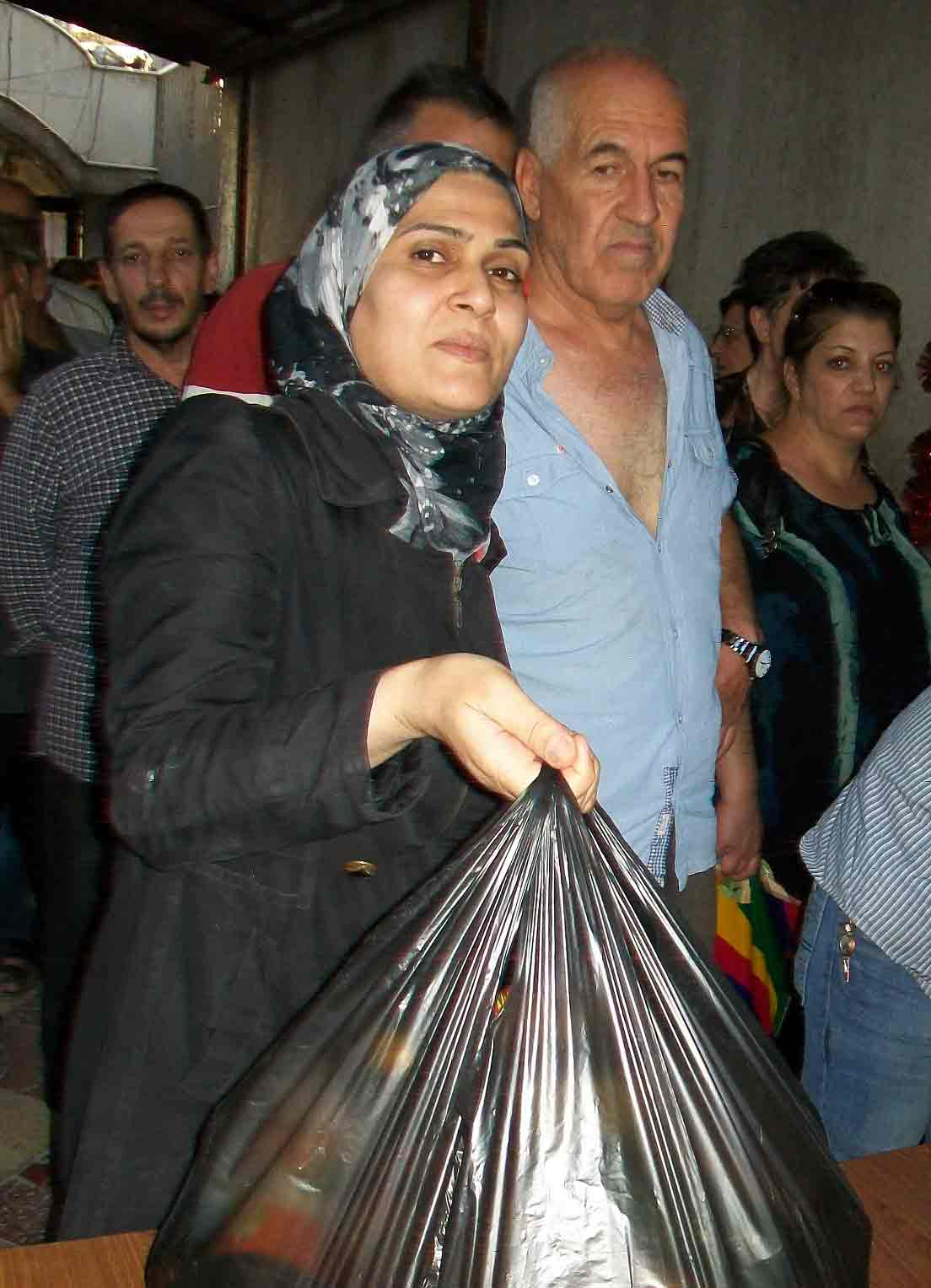 A Syrian woman collects food aid from a church at a previous distribution.