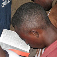 Believers read a Bible given to them during a distribution in Uganda where many face attacks from Muslim radicals.