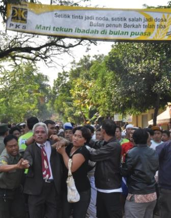 "Police attempted to protect Christians of another church in Indonesia, but two of the church's pastors were beaten by the mob. The banner, carried by a radical reads ""The Muslim community rejects the building of a church in Mustika Jaya."""