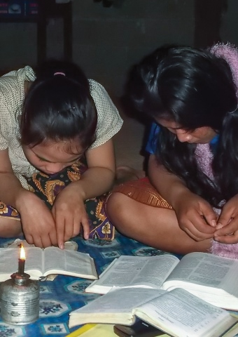 Two young Lao girls read Bibles