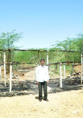 "Pastor Ruben stands in front of ""The Church of South India"" which was burned down on March 18."