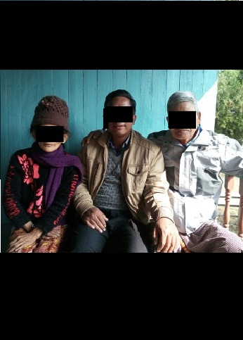 "A Christian worker sits between Pastor ""Kam"" and his wife."