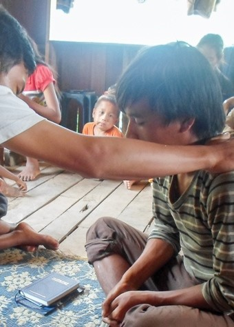 A Christian in Laos prays for a young boy.