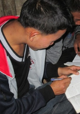 A young man from Laos studies the Bible with several others where the Christians are often persecuted for their faith by their families.