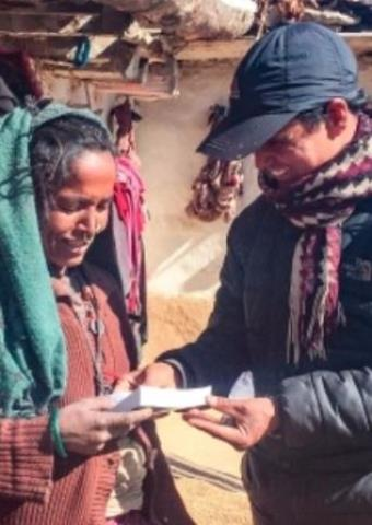 A front-line worker giving a Nepali woman a Bible.