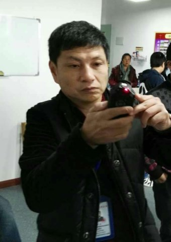 A Chinese official takes photos during a raid on a house church.